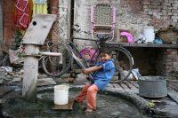 Boy fills up his bucket in Varanasi, India (c) Bart Coolen