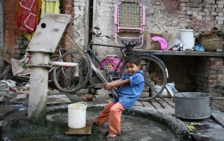 Boy fills up his bucket in Varanasi, India (c) Bart Coolen