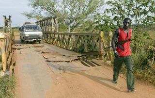 Armed man crosses a bridge in South Sudan, Juba. Minefields South Sudan (c) Bart Coolen www.bartcoolen.nl